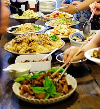 大皿に盛りつけられた台湾料理を取り分けるお客様