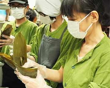 協力しながら丁寧に台湾ちまきを笹の葉で包むスタッフ
