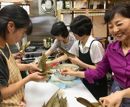 一つ一つ丁寧に台湾ちまきを笹の葉で包む女性スタッフ