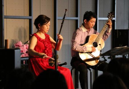 美しい衣装をまとい二胡とギターを演奏する出演者